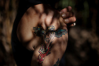 """Ventura, California, July 23, 2010 - A portrait of Tim 'Timbow' Bowman's tattoo in honor of his daughter. In 1987 Bowman's 18-month-old daughter, Miranda Laurel, died from Lyme disease. He wrote about his daughter, """"Angels come in many forms. Some are as close as your friends. The Angels I have tatt[oed] are for my Daughter who died. I will carry my cross to[sic] the day I die! I will see you honey when I walk the Gates [of] Heaven!"""" His wife left him after the death. A year later he fell through a plate glass window while working on a construction site, leaving him disabled and unable to work construction. He says the loss of his wife and daughter and his struggles with work sent him into a spiral. He eventually lost his home. Bowman has been homeless and living in a camp along the Ventura River bottom since the early 1990's. He says he lives in the 300+ community along the river bottom because he """"feels at home."""" Adding, """"I feel loved down here. Up there is nothing but trouble."""" The two-mile stretch of river bottom from the Pacific to Stanley Road is home to about 300 homeless, who have carved tunnels and paths into the tall grass and bamboo. Bowman, who survives off of SSI, says, """"I lead an honest life. I don't steal, I don't rob and I share whatever I can."""" ."""