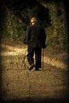 An elderly man with a cane walking along seawall.