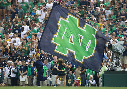 August 31, 2013:  Notre Dame cheerleader runs with the flag during NCAA Football game action between the Notre Dame Fighting Irish and the Temple Owls at Notre Dame Stadium in South Bend, Indiana.  Notre Dame defeated Temple 28-6.