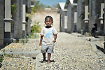 "A child stands on a path amid houses in a model resettlement village constructed by the Lutheran World Federation in Gressier, Haiti. The settlement houses 150 families who were left homeless by the 2010 earthquake, and represents an intentional effort to ""build back better,"" creating a sustainable and democratic community. This boy and his mother are among the residents."