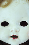 Close up of white face of 1950s doll with black holes where her eyes should be and open mouth and untidy hair