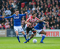 Lincoln City's Bruno Andrade gets between Macclesfield Town's Michael Rose, left, and Zak Jules to earn the free kick that lead to Lincoln City goal<br /> <br /> Photographer Andrew Vaughan/CameraSport<br /> <br /> The EFL Sky Bet League Two - Lincoln City v Macclesfield Town - Saturday 30th March 2019 - Sincil Bank - Lincoln<br /> <br /> World Copyright © 2019 CameraSport. All rights reserved. 43 Linden Ave. Countesthorpe. Leicester. England. LE8 5PG - Tel: +44 (0) 116 277 4147 - admin@camerasport.com - www.camerasport.com