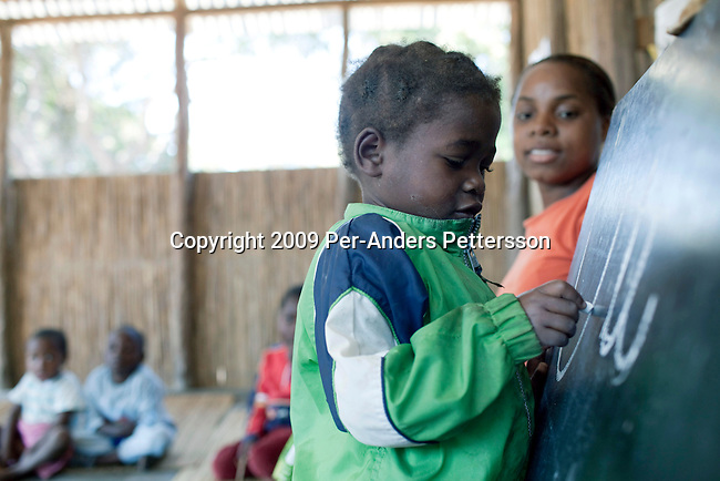 MACHALUCUANE, MOZAMBIQUE - JULY 14: Castera Joao, age 4, and an orphan, writes on a chalkboard as her teacher Isabel looks on, during a class in a primary school on July 14, 2009, in Machalucuane, Mozambique. The village is located about 18 miles outside Xai-Xai, in Gaza province in Mozambique. The villagers have about 7 miles to the nearest hospital and secondary school. The school was funded by Save The Children USA money and the organization has many projects in the province and around Mozambique. (Photo by Per-Anders Pettersson/Getty Images) ......