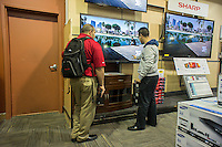 "Last minute shoppers browse flat screen televisions in a Best Buy store in the borough of Queens in New York on Saturday, December 22, 2012 looking for bargains. ""Super Saturday"", the Saturday prior to Christmas, is the second busiest shopping day of the year.  (© Richard B. Levine)"