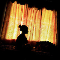 A young girl sits in front of a curtained window in Mindo, Ecuador, 27 September 2014.