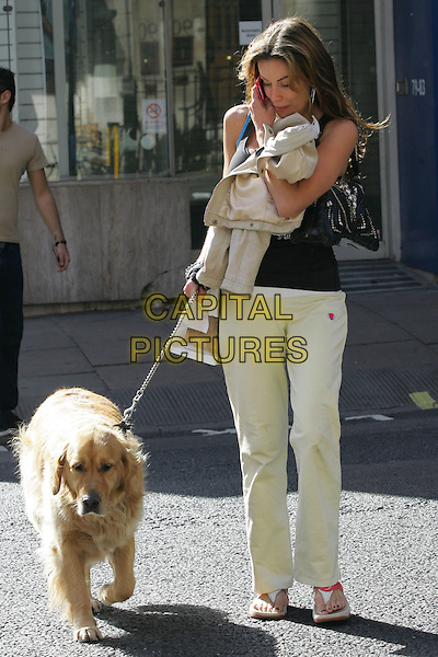 JO-EMMA LAVIN.Spotted walking her dog in London, England..September 10th, 2009.full length animal pet talking on mobile phone profile white cream trousers black tank top flip flops sandals .CAP/GM.©GM/Capital Pictures.