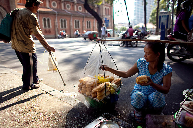 "Linh sells fried egg breakfast sandwhiches called ""Banh mi op-la"" in the park in downtown Ho Chi Minh City...Kevin German / LUCEO"