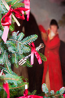 Close up of the Christmas tree decorated with red bows and antique silver teaspoons