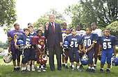 (FIRST OF TWO PHOTOS) United States President George W. Bush, surrounded by Washington, D.C.-area Pop Warner League players in the White House Rose Garden, Sunday, September 9, 2001, displays a coin before tossing it to decide which teams would kickoff games on opening day of the National Football League's regular season. The coin landed tails side up. <br /> Mandatory Credit: Tina Hager / White House via CNP