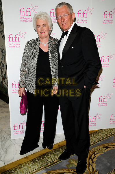 MARGARET MOUNTFORD & NICK HEWER.The FIFI UK Fragrance Awards 2008 at the Dorchester Hotel, Park Lane, London, England..April 23rd 2008.full length trousers black silver grey gray pattern jacket pink clutch bag purse tuxedo glasses .CAP/CAN.©Can Nguyen/Capital Pictures.