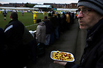 A home supporter with a tray of chips and ketchup watching the action during the first-half at Victory Park, as Chorley played Altrincham (in yellow) in a Vanarama National League North fixture. Chorley were founded in 1883 and moved into their present ground in 1920. The match was won by the home team by 2-0, watched by an above-average attendance of 1127.