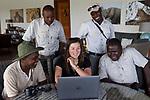 Cheetah (Acinonyx jubatus) biologist, Xia Stevens, reviewing photographs from lodge guides, Moses Mwale, Lexon Munuma, Mullah Maipenzi, and Joseph Sandala, to identify individual cheetahs, Kafue National Park, Zambia