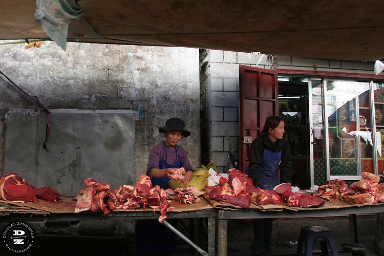 Merchants sell large cuts of yak meat at an outdoor market in the Barkhor area of Lhasa, Tibet.  Photograph by Douglas ZImmerman
