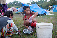 Nepali Child washes dishes. Thousands of people in Nepal have arranged  shelter camps away from the rubble following the second earthquake shock. A 7.3 magnitude earthquake killed at least 37 people and spread panic in Nepal on Tuesday, bringing down buildings already weakened by a devastating tremor less than three weeks ago and unleashing landslides in Himalayan valleys near Mount Everest. Kathmandu, Nepal. May 13, 2015