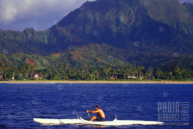 Man paddling one-man canoe off  Hanalei Beach, Hanalei Bay, North Shore, Kauai, Hawaii
