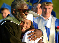 BENSALEM, PA - JUNE 18: Dean of Students Lorenzo Henderson (L) hugs Alexia G. Kohler before she receives her diploma during Bensalem High School's 90th Annual Commencement ceremony June 18, 2014 at Bensalem Memorial Stadium in Bensalem, Pennsylvania. About 500 students graduated. (Photo by William Thomas Cain/Cain Images)