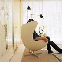 A man sits in a white leather Egg chair by Arne Jacobsen in a corner of the living room