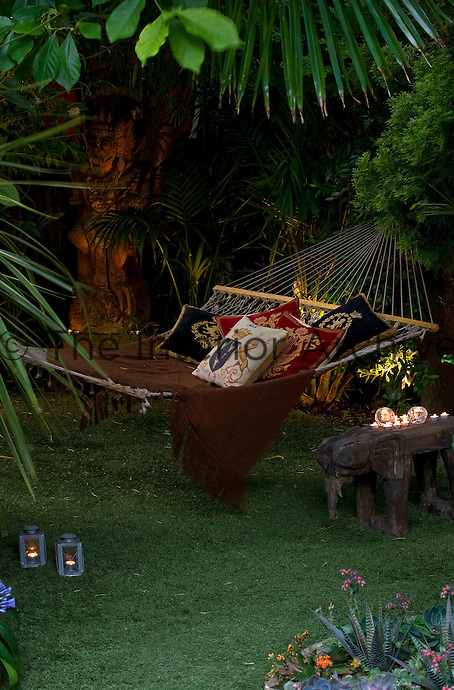 Tealights and subtle garden lights create a romantic ambience around the hammock