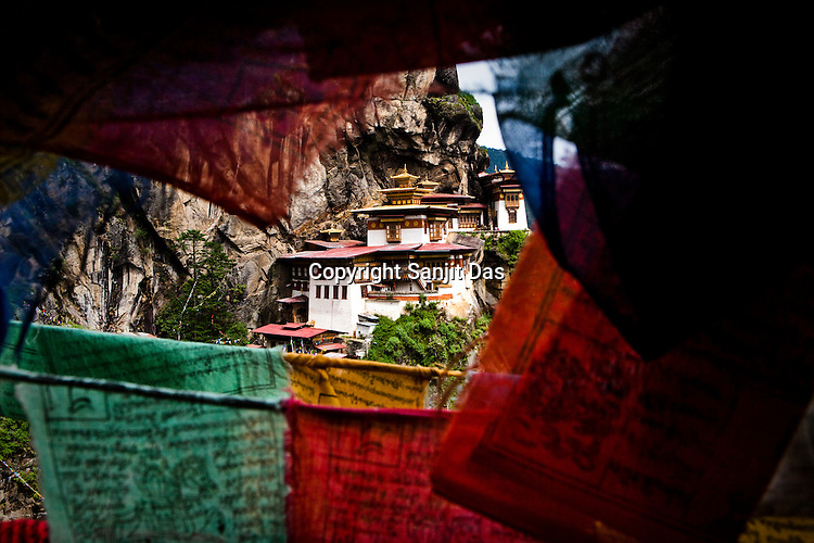 Seen through the prayer flags Taktsang Temple, also known as The Tiger's Nest Temple is a prominent Buddhist temple complex, located in the cliffside of the upper Paro valley, Bhutan. This temple complex was first built in 1692, around the Taktsang Senge Samdup cave where Guru Padmasambhava is said to have meditated for three months in the 8th century.