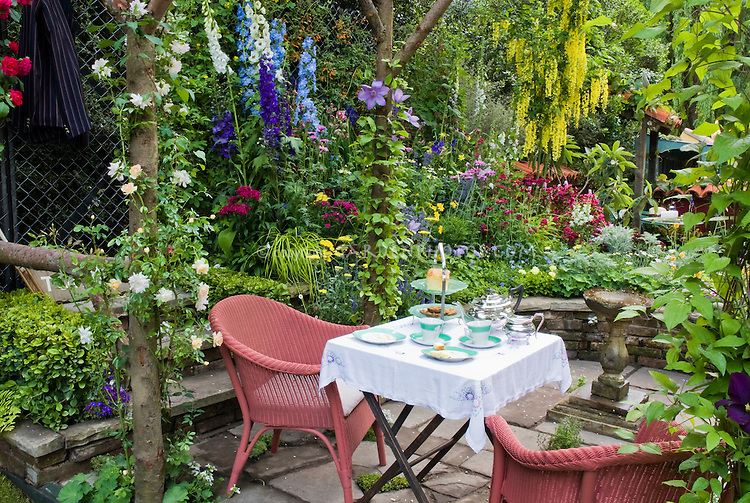 Dining outside in the garden plant flower stock for Tiny garden rooms