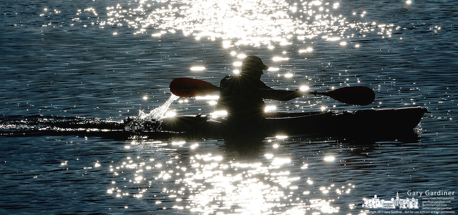 Kayaker on lake at sunrise in light fog