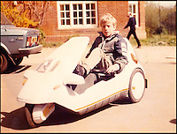 BNPS.co.uk (01202 558833)<br /> Pic: GrantSinclair/BNPS<br /> <br /> Grant Sinclair in a C5 when he was a boy.<br /> <br /> The much-maligned Sinclair C5 electric tricycle that fell flat on its face in the 1980s has been reborn by the original inventor's nephew. <br /> <br /> Eccentric businessman Sir Clive Sinclair is famous for some groundbreaking inventions but none more so than his disastrous one person vehicle.<br /> <br /> Sir Clive touted his plastic-covered tricycle as a leap in personal transportation only for it to be reviewed as one of the greatest marketing bombs of post-war Britain. <br /> <br /> Grant Sinclair has kept faith in his uncle's memorable design and has spent the last four years reimagining it in the hope his fairs better in a world where bike lanes are common place.