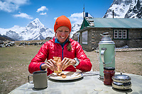 A woman sits putting nut butter on a pancake at a Nepali guesthouse in Dzongla, while trekking in the Khumbu Valley, Nepal.