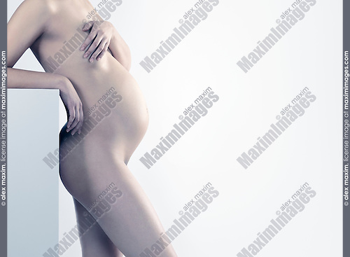 Beautiful naked pregnant woman side view isolated on gray background in light pastel colors