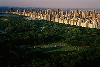 Shadows sweep across Sheep Meadow, a 15-acre space where people congregate for picnics on Sunday afternoon. Until 1934, a shepherd stopped traffic on the west drive so his flock could travel to and from their meadow.  Photograph shows buildings on the east side of Central Park line the perimeter of the park.  The entire perimeter of the park is surrounded by tall buildings and urban life.<br /> <br /> When Central park was planned, most New Yorkers still lived below 38th Street in crowded, chaotic quarters. Frederick Law Olmsted planned the park with Calvert Vaux as a refuge from urban stress. The design of Central Park embodies Olmsted's social consciousness and commitment to egalitarian ideals.