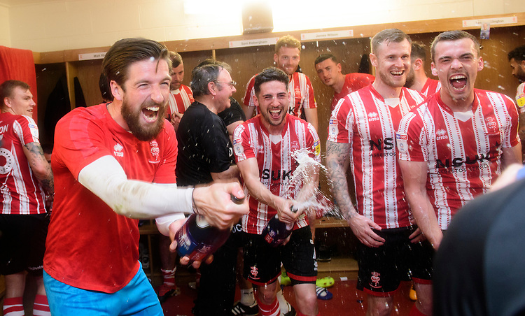 Lincoln City's Josh Vickers, left, and Lincoln City's Tom Pett spray champagne as the Imps' players celebrate winning the league<br /> <br /> Photographer Chris Vaughan/CameraSport<br /> <br /> The EFL Sky Bet League Two - Lincoln City v Tranmere Rovers - Monday 22nd April 2019 - Sincil Bank - Lincoln<br /> <br /> World Copyright © 2019 CameraSport. All rights reserved. 43 Linden Ave. Countesthorpe. Leicester. England. LE8 5PG - Tel: +44 (0) 116 277 4147 - admin@camerasport.com - www.camerasport.com