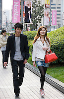 Couple walking on Nanjing Road, central Shanghai, China