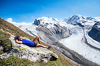 A woman lays on a rock relaxing in the sun with views of the Monte Rosa, Switzerland.