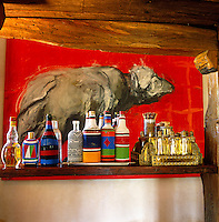 Bottles in beaded cases line the bar in front of a large painting by Tonio Trzebinski