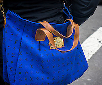 A woman carries a handbag with a Louis Vuitton label in New York on Thursday, December 4, 2014.(© Richard B. Levine)