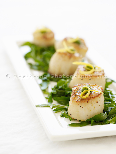 Scallops on a bed of greens.