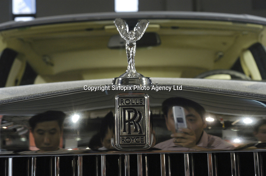 Visitors look at a Rolls-Royce car at the Auto China exhibition in Beijing, China. China's booming economy has led to rocketing car production and sales, with car makers from all over the world seeking a piece of the action.