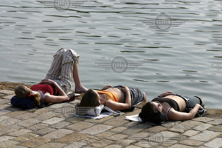 Girls relaxing at the river bank of river Guadalquivir. Seville, Andalucia, Spain.