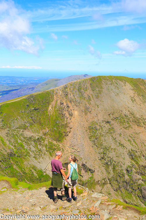 Man and woman enjoying view from summit of Mount Snowdon, Gwynedd, Snowdonia, north Wales, UK