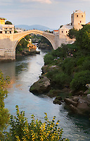 View along the river of the old reconstructed bridge. Sunset late afternoon light. Historic town of Mostar. Federation Bosne i Hercegovine. Bosnia Herzegovina, Europe.