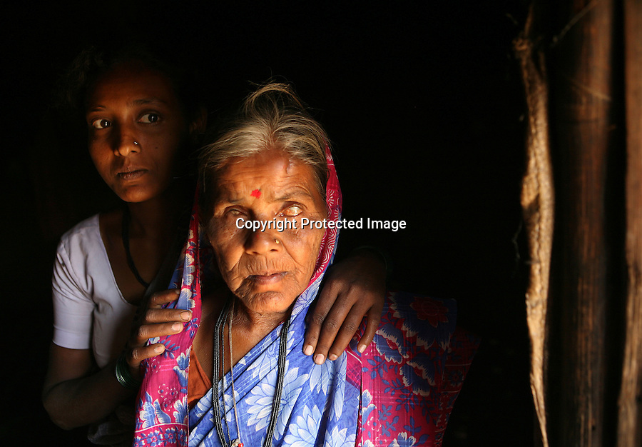 "Lalita Kamble, 50,  is photographed in the doorway of her home with her niece.  Kamble went blind at a young age and so, when she was eight years old, her parents dedicated her as a Devadasi.  ""They said you can be buried as a married person now because you're married to Yellamma,"" she says, referring to the ritual of burying unmarried women in a lying down position while married women are buried sitting up. ""I wished I could get married but I knew no man would marry because because of my blindness,"" she adds. Through a dairy program set up  by an organization called Vimochana Sangha which was founded to dismantle the Devadasi system, Kamble now takes care of a water buffalo and makes some income from the sale of its milk. Despite her acceptance of her lot in life, she does not support the continuation of the Devadasi system."