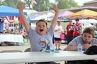 MEGAN DAVIS MCDONALD COUNTY PRESS/Ten-year-old Clayton Hosier threw his hands up and showed the audience an empty mouth - officially winning the Donut Eating Contest last year - as a competitor looks on with a mouth full of donut. Hosier ate three donuts in a minute and a half.