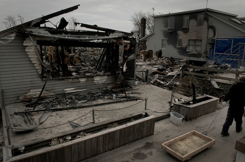 A boy from Breezy Point, NY is dragging an empty makeshift cart in the devastated by Hurricane Sandy area. More than 80 homes were destroyed and 110 burned to the ground this night.