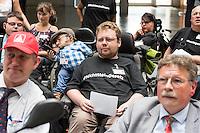 """SPD-Fachtagung zum geplanten Bundesteilhabegesetz am Montag den 30. Mai 2016 in Berlin.<br /> Unter dem Titel """"Selbstbestimmt und mittendrin – das Bundesteilhabegesetz kommt"""" fuehrte die SPD-Bundestagsfraktion im Paul-Loebe-Haus eine Fachtagung zum neuen Bundesteilhabegesetz durch.<br /> Vorgestellt wurde der Entwurf des Bundesteilhabegesetzes und die darin enthaltenen wichtigsten Neuerungen.<br /> Etliche betroffene Menschen mit Behinderung nahmen an der Fachtagung teil und kritisierten den Gesetzentwurf scharf. Fuer sie bedeuten etliche Neuerungen Verschlechterungen fuer ihre Lebenssituationen und den Ausschluss an gesellschaftlicher Teilhabe. Sie protestierten mehrfach waehrend der Tagung laustark gegen das Gesetz.<br /> Im Bild mit kariertem Hemd: Der Aktivist und Fernsehmoderator Raul Krauthausen.<br /> 30.5.2016, Berlin<br /> Copyright: Christian-Ditsch.de<br /> [Inhaltsveraendernde Manipulation des Fotos nur nach ausdruecklicher Genehmigung des Fotografen. Vereinbarungen ueber Abtretung von Persoenlichkeitsrechten/Model Release der abgebildeten Person/Personen liegen nicht vor. NO MODEL RELEASE! Nur fuer Redaktionelle Zwecke. Don't publish without copyright Christian-Ditsch.de, Veroeffentlichung nur mit Fotografennennung, sowie gegen Honorar, MwSt. und Beleg. Konto: I N G - D i B a, IBAN DE58500105175400192269, BIC INGDDEFFXXX, Kontakt: post@christian-ditsch.de<br /> Bei der Bearbeitung der Dateiinformationen darf die Urheberkennzeichnung in den EXIF- und  IPTC-Daten nicht entfernt werden, diese sind in digitalen Medien nach §95c UrhG rechtlich geschuetzt. Der Urhebervermerk wird gemaess §13 UrhG verlangt.]"""