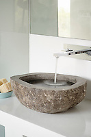 Water runs from a stainless steel tap into a rustic stone washbasin.