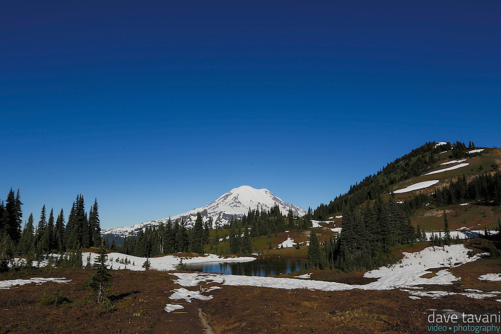 A small lake sits at the foot of Naches Peak with Mt. Rainier in the distance.