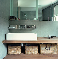 The walls of the main bathroom are lined with pale grey stone contrasting with the large mirrors and a scrubbed wooden bench supporting the contemporary wash basin