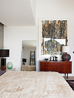 A large abstract painting hangs above an original Scandinavian mid-century chest of drawers in the master bedroom