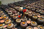 "Workers pour tens of thousands of soybeans into large clay jugs as they create soy sauce.  Aerial photographs of the soy sauce factory show hundreds of the jugs laid out in rows and factory workers can be seen filling them with golden-coloured soybeans after a roasting process.<br /> <br /> Amateur photographer Nghiem Dinh Chinh, who captured these shots in Hung Yen, Vietnam, said: ""Soybean seeds are soaked in water and then dried.  SEE OUR COPY FOR DETAILS.<br /> <br /> Please byline: Nghiem Dinh Chinh/Solent News<br /> <br /> © Nghiem Dinh Chinh/Solent News & Photo Agency<br /> UK +44 (0) 2380 458800"