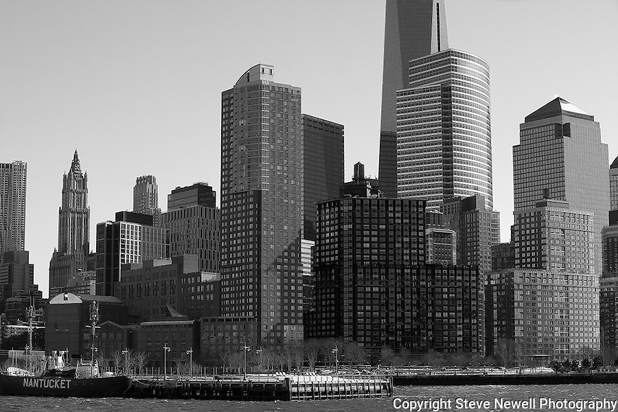 """Skyscrapers"" Black and White Downtown Manhattan New York. I shot this Downtown Manhattan Skyline scene while on a boat tour in the days before the worst storm in 20 years blew in lasting three days. The strong winds made it difficult to stay warm, hold my camera stable on my monopod and stay out of the water spray from the waves created by the boat. The New World Trade Center tower was just finishing construction at the top and rises high above the other skyscrapers. During the storm Governors in surrounding states and New York banned driving personal vehicles on the public highways for a couple days.  Being from Lake Tahoe I came prepared for the weather and was excited to capture New York City and Central Park with fresh snow. The incredible skyline of Manhattan was breathtaking. Growing up in California, visiting San Francisco as an adult regularly and shooting it many times as a professional photographer didn't prepare me for the magnitude of the impressive size and quantity of the buildings and skyscrapers that form the skyline of Manhattan. My hat is off to the Architects and Engineers who contributed to building the touted greatest city on Earth. Black and white photography is still my favorite so you will see many images offered in Color and BW."
