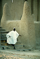 Man in flowing white robe, emerges from mosque in Mali, Africa. Islam. Moslem. Imam. Religions. architecture. Mali Africa.